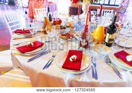 Table set for banquet with cutlery. Cotton flower decoration.
