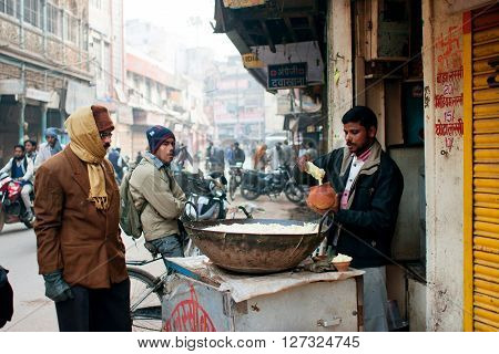 VARANASI, INDIA - JANUARY 4, 2013: People watch with attention to the seller of street food at the cold morning on January 4, 2013 in Varanasi. Varanasi urban agglomeration had a population of 1435113