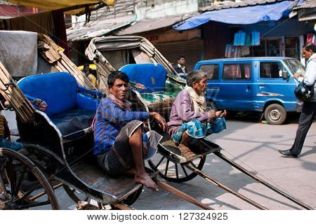 KOLKATA, INDIA - JANUARY 10, 2013: Elderly workers of hand-pulled rickshaw sit outdoor and wait for the passengers on January 10, 2013. Kolkata's road space was only 6 perc. compared to 23 perc. in Delhi