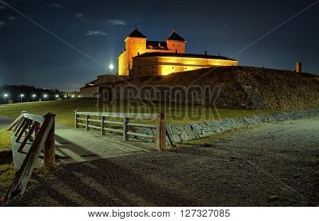 Night scene with medieval castle at moonlit night. Wooden bridge leading to stone built fortress in Finland.
