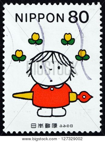 JAPAN - CIRCA 1998: a stamp printed in the Japan shows Child with Ink Pen Flowers Overhead Letter Writing Day circa 1998