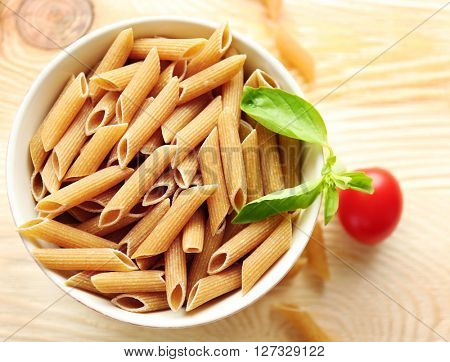 Dry brown penne pasta in white bowl on wooden table