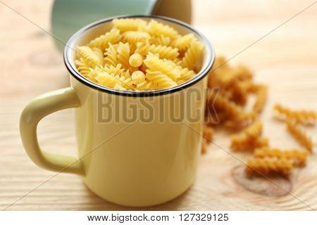 Dry fusilli pasta in metallic mug on wooden table
