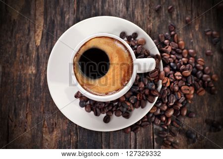 Cup of hot coffee with roasted beans on rustic wooden background