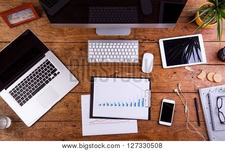Desk with gadgets, office supplies and chart graph. Computer keyboard, notebook, smart phone and stationery around the workplace. Flat lay. Studio shot on wooden background.