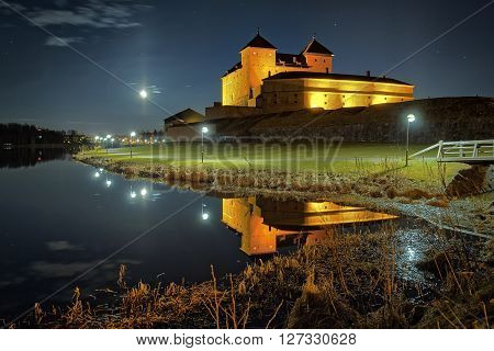 Night scene with medieval castle by the lake in Finland. The moon shining on clear night sky and reflection of the castle in the water.