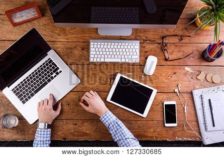 Business person at office desk. Smart watch on hand,  working on laptop. Smart phone, tablet and various office supplies around the workplace. Flat lay.