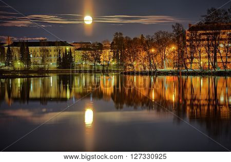 Cityscape of Hämeenlinna in Finland at moonlit night. Reflections of citylights on the still water of the lake and the moon on the sky.