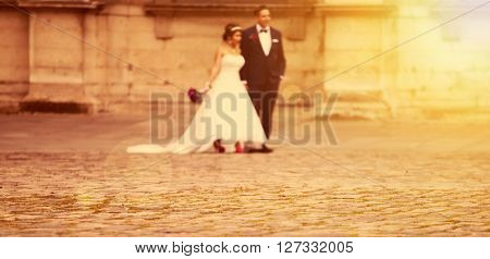 Blurred background of groom and bride in the sunset