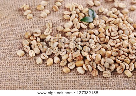 Green coffee beans on sackcloth material.