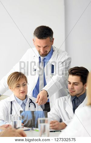 Medical doctors sitting at the meeting in modern hospital