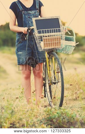 Young woman with bicycle in meadow. Retro style