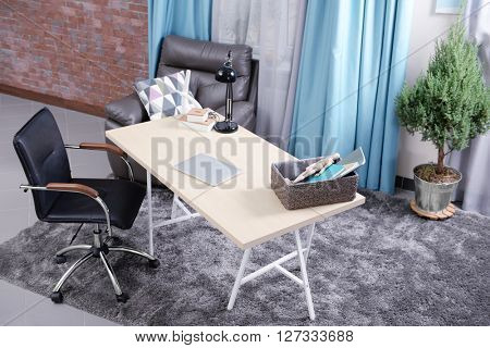 Workplace with table, office chair and laptop in living room