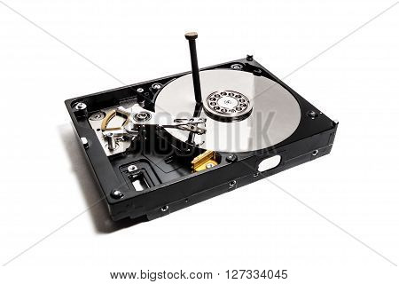 the hard drive from the computer with hammered nail on white background