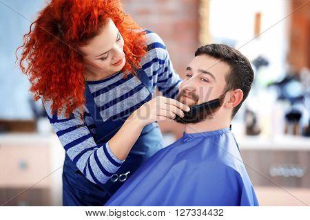 Professional hairdresser combing man beard
