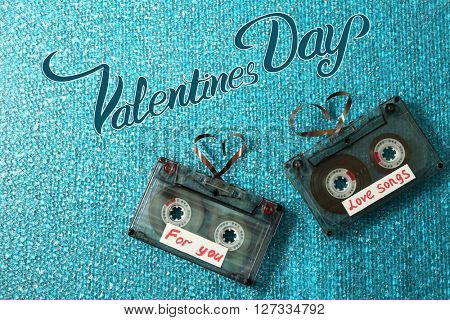 Retro audio cassettes with tapes in shape of hearts on blue textured background