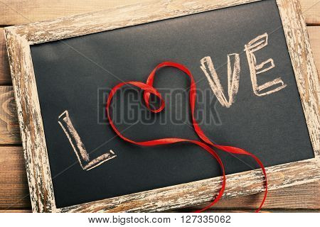 Love written on chalkboard, close-up. Retro style