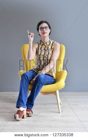 Woman in yellow armchair pointing at message