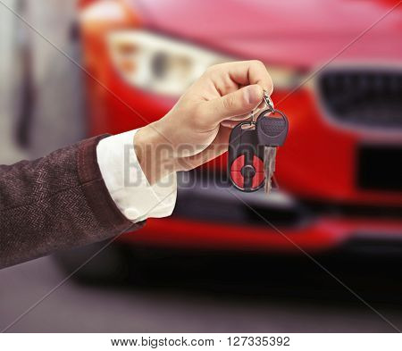 Male hand holding car keys on car background