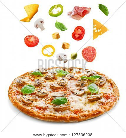 Tasty pizza with vegetables and falling ingredients isolated on white