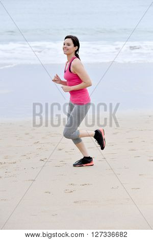 Fitness woman jogging on the beach
