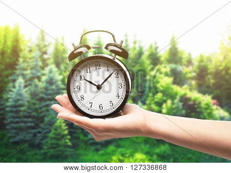 A retro alarm-clock on female hand, forest background