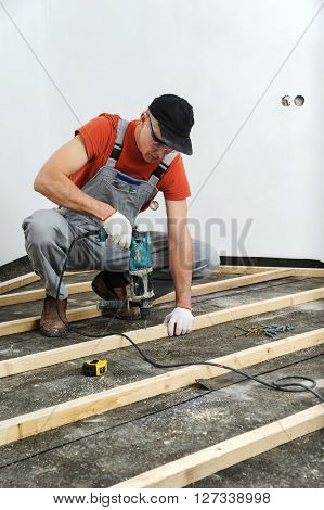 Worker drill holes in the wooden beams using an electric drill.
