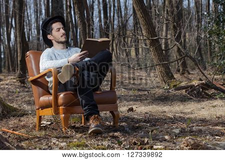 young man reads a novel in the woods, portrait