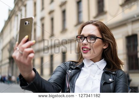 City lifestyle stylish hipster girl using a smartphone taking photo selfie with camera in a street