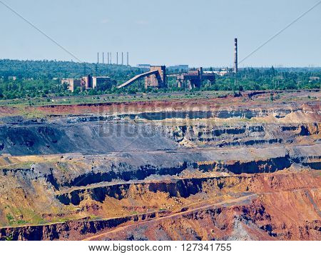 Upper levels of the iron ore open cast mine with crushing plant and pipes one the background