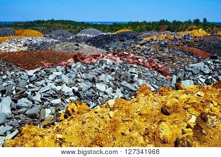 Colorful dumps of depleted iron ore with trees on background