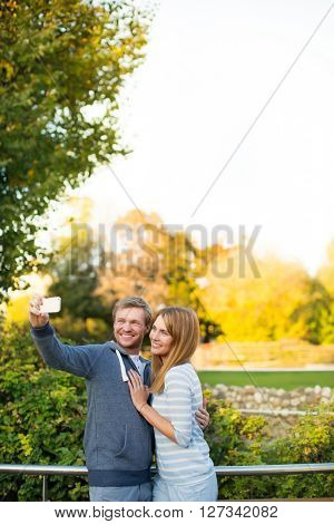 Smiling couple making selfie outdoors