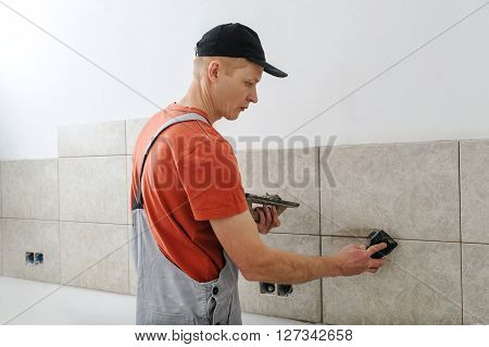 Worker holding a rubber float and filling joints with grout.