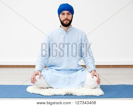 Meditation. Portrait of a young bearded yogi man in a turban, hands laying on the knees, sitting on the sheep skin in a lotus pose