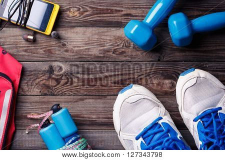 Sports equipment - sneakers, skipping rope, dumbbells, smartphone and headphones.