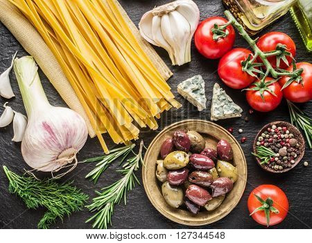 Pasta ingredients. Cherry-tomatoes, spaghetti pasta, rosemary and spices on a graphite board.