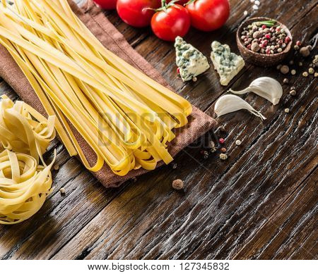 Pasta ingredients. Cherry-tomatoes, spaghetti pasta and blue cheese  on the wooden table.