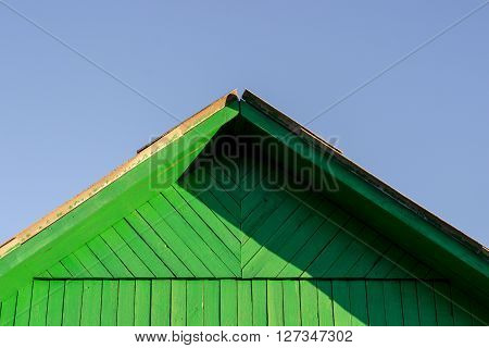 Triangular shaped wooden woof painted in green with clear blue sky and shadows from the setting sun. Copy space area.