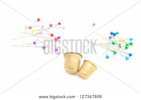 Colored Pins And Thimbles On White