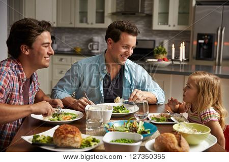 Male gay couple and daughter dining in their kitchen