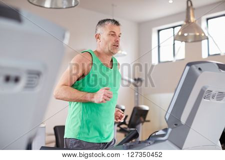 Mature Man Running On Treadmill In Gym