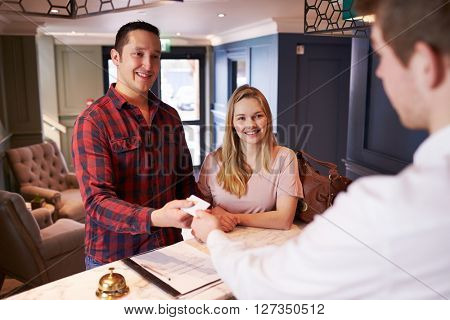 Couple Checking In At Hotel Reception Desk