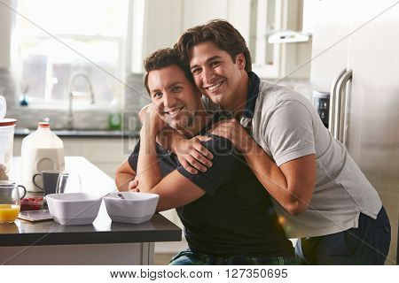 Male gay couple embracing in their kitchen, side view