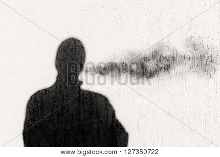 Blurred shadow effect of a man exhaling smoke. Image of the shadow appears on a rough surface wall.