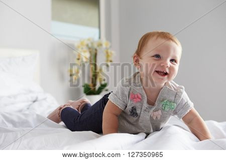 A happy baby girl crawling on a bed, copy space on left