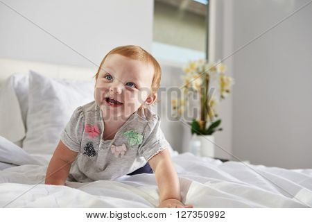 A happy baby girl crawling on a bed, copy space on right