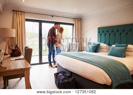 Couple Arriving In Hotel Room On Vacation
