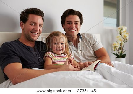 Young girl in bed with her male parents, looking to camera