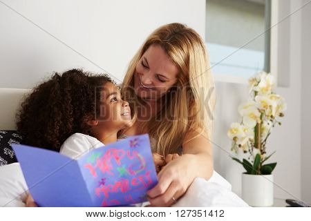 Caucasian mum and black daughter, looking at each other