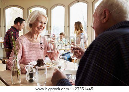 Senior Couple Enjoying Dessert In Restaurant Together